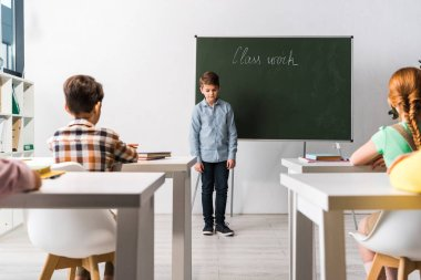 schoolkids sitting at desks near classmate near chalkboard with class work lettering
