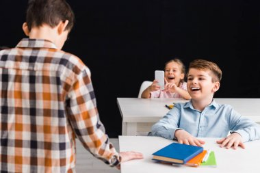 selective focus of schoolgirl taking photo of classmate while schoolboy laughing isolated on black, cyberbullying concept