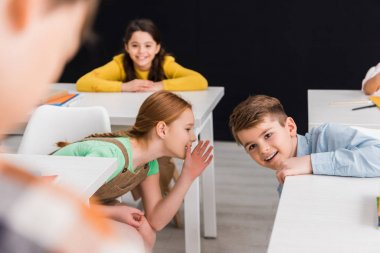 selective focus of schoolkids gossiping near classmate isolated on black, bullying concept