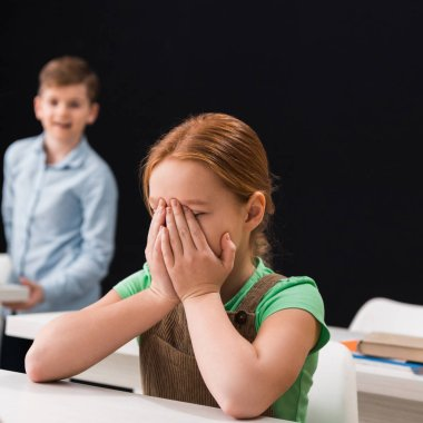 selective focus of upset kid crying near classmate isolated on black, bullying concept