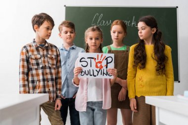 selective focus of schoolchildren looking at classmate holding placard with stop bullying lettering