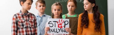 panoramic shot of schoolchildren looking at classmate holding placard with stop bullying lettering
