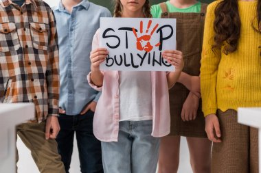 cropped view of schoolchildren standing near classmate holding placard with stop bullying lettering