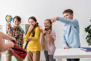 selective focus of cruel schoolkids pointing with fingers at bullied classmate