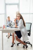 zamyšlená a sexy sestřička v brýlích sedí v blízkosti žen v bílých pláštích v laboratoři