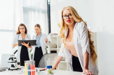 selective focus of sexy nurse in glasses and white coat near women in laboratory