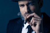 Fotografie Porträt eines Mafioso, der Zigarre raucht und in die Kamera auf dunkelblauem Hintergrund blickt
