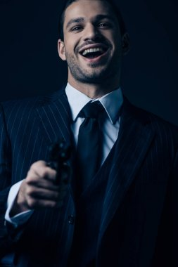Selective focus of gangster aiming gun, laughing and looking at camera isolated on dark background stock vector