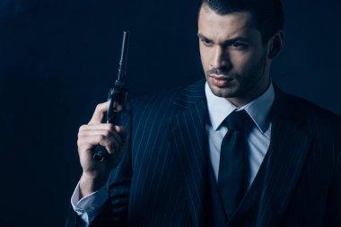 Pensive gangster raising gun on dark blue background stock vector