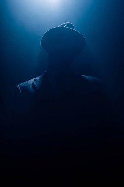 Silhouette of dangerous mafioso in suit and felt hat on dark background stock vector