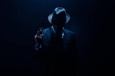 Silhouette of gangster raising gun on dark blue background stock vector