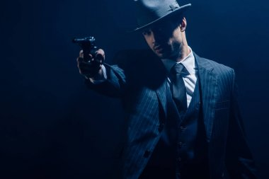 Gangster aiming weapon with outstretched hand on dark background