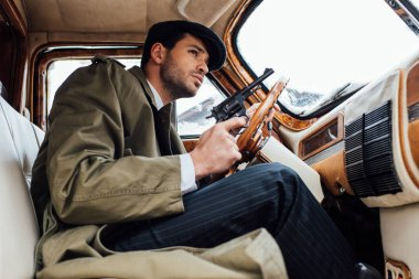 Low angle view of mafioso holding gun and driving car stock vector