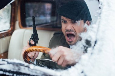 Selective focus of angry gangster with gun driving car stock vector