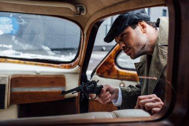Selective focus of mafioso aiming gun and looking into retro car stock vector