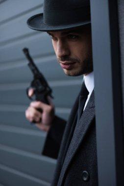 Selective focus of mafioso with gun in corner near wall on street stock vector
