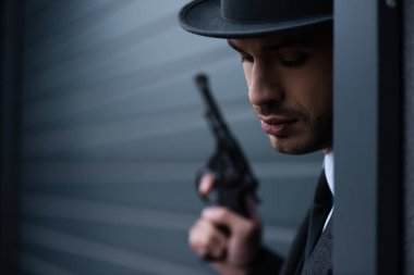 Selective focus of gangster with weapon in corner near wall on street stock vector