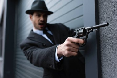 Selective focus of mafioso aiming gun with outstretched hand near wall on street stock vector