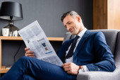 usmívající se obchodník v obleku sedí v křesle a čte noviny s obchodním nápisem