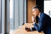 boční pohled zamyšleného podnikatele v obleku držícího sklo a dívajícího se oknem