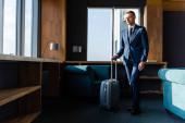 schöner Geschäftsmann im Anzug mit Reisetasche im Hotel