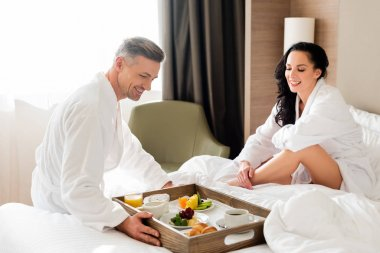 Boyfriend bringing breakfast in bed for smiling girlfriend in hotel stock vector