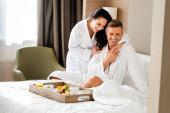 smiling girlfriend in bathrobe hugging handsome boyfriend in hotel