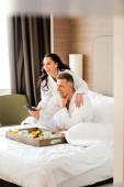 lächelnde Freundin im Bademantel umarmt schönen Freund mit Fernbedienung im Hotel