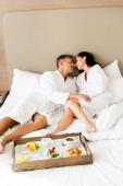 Freund und Freundin in Bademänteln küssen sich in der Nähe Tablett mit Essen im Hotel