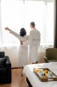 zpět pohled na přítele a přítelkyni v županech objímání a pohled koryto okna v hotelu