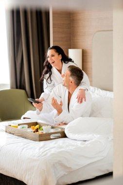 Smiling girlfriend in bathrobe hugging handsome boyfriend with remote controller in hotel stock vector