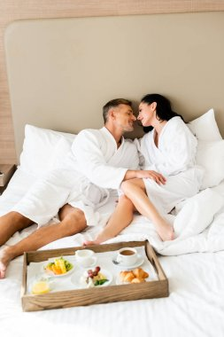 Boyfriend and girlfriend in bathrobes kissing near tray with food in hotel stock vector