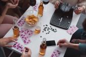Kyjev, Ukrajina - 27. ledna 2020: oříznutý pohled na přátele sedící u stolu s dávkovačem loterijních míčků, karty, krycí čipy a smartphone s prázdnou obrazovkou