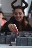 Kyjev, Ukrajina - 27. ledna 2020: selektivní zaměření usměvavé dívky v kostýmu s černými rohy držící figurku hračky při hraní labyrintu deskové hry