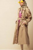 Fotografie stylish african american girl in sunglasses with flowers, head scarf and trench coat standing with hands in pockets on beige