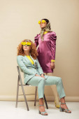 redhead woman in sunglasses with flowers sitting on chair near stylish african american girl posing on beige