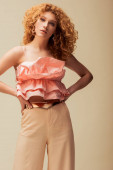 attractive redhead woman standing with hands on hips isolated on beige