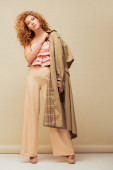 stylish redhead woman in ruffled top and trousers holding trench coat while posing on beige