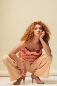 attractive redhead woman in ruffled top and trousers sitting on beige