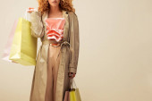 cropped view of stylish redhead woman in ruffled top, trousers and trench coat holding shopping bags isolated on beige