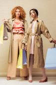 beautiful multicultural girls in trench coats standing with shopping bags on beige