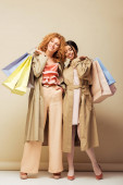 happy multicultural girls in trench coats holding shopping bags on beige