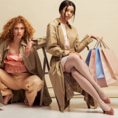 curly redhead woman near african american girl sitting on chair with shopping bags on beige