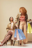happy redhead woman laughing with african american girl sitting on chair with shopping bags on beige
