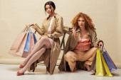 curly redhead woman posing near african american girl sitting on chair with shopping bags on beige