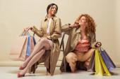 šťastná zrzka žena usmívá s africkou americkou dívkou sedí na židli s nákupními taškami na béžové