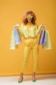 stylová zrzka žena v slunečních brýlích s květinami drží nákupní tašky na žluté