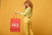 Fotografie stylische rothaarige Frau berührt Sonnenbrille mit Blumen und hält Einkaufstasche mit Verkauf Schriftzug auf gelb