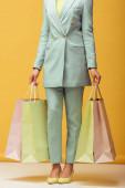Afričanky americká dívka v obleku drží nákupní tašky na žluté