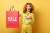 fröhliche rothaarige Frau zeigt mit dem Finger auf Einkaufstasche mit Verkaufsaufdruck auf gelb